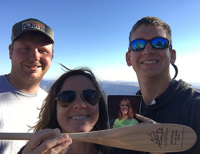 Morgan Cowles (from left), Jennifer Deignan holding a picture of teammate Caitlin Nash and Justin Gilliland pose at the Grand Canyon.